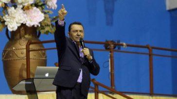 pastor evangélico de la iglesia La Cosecha en Honduras, Misael Argeñal, levanta la mano frente a su congregación