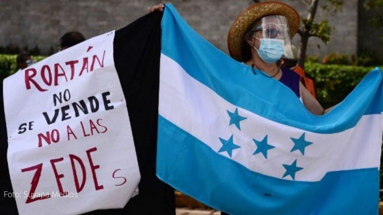 mujer con bandera en mano exigiendo no a las zedes