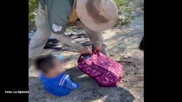 niño de camisa azul y mochila rosada es ayudado por persona
