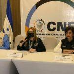 los consejeros del Consejo Nacional Electoral, Kelvin Aguirre, Ana Paola Hall y Ricci Moncada en una mesa durante una conferencia de prensa y de fondo el logo del CNE