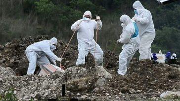personal de sinager vestidos de blanco escavan tumbas