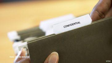 mujer sostiene en sus manos un documento confidencial