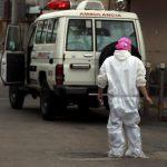 personal de salud con trajes de protección contra el covid resguarda ambulancia en Honduras