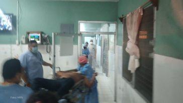 hombre herido de bala sobre camilla es atendido por personal medico en olanchito, yoro