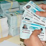 mujer sostiene en sus manos tarjetas de identidad