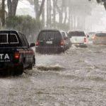 carros pasan por inundadas calles en honduras por lluvias