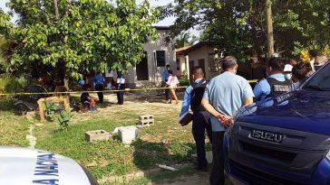 agentes policiales y personas observan casa en donde se suscito una masacre en puerto cortes