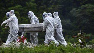 personas usan trajes especiales para enterrar a persona con covid
