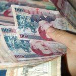 Una persona sostiene un fajo de dinero entre sus manos