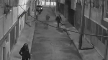 tres personas caminan por callejon, entre ellos un ladrón que atacó a joven por robarle el celular en colombia
