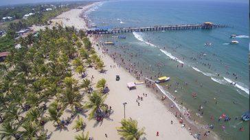 gente caminando por la playa, al igual que personas nadando en la playa