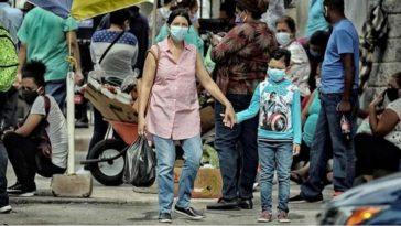 mujer con niño tomado de sis manos caminando en el mercado