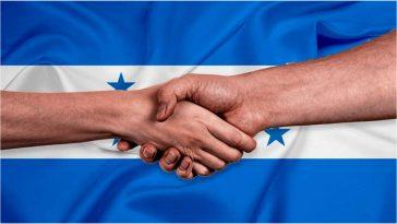 Dos personas se dan la mano como motivo de un acuerdo. Al fondo, la Bandera Nacional de Honduras.