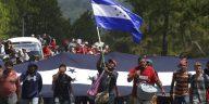 migrantes hondureños con bandera en mano