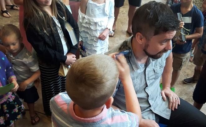 Children and young people watch as several take turns clipping pastor Justin Caruthers' hair after a successful challenge.
