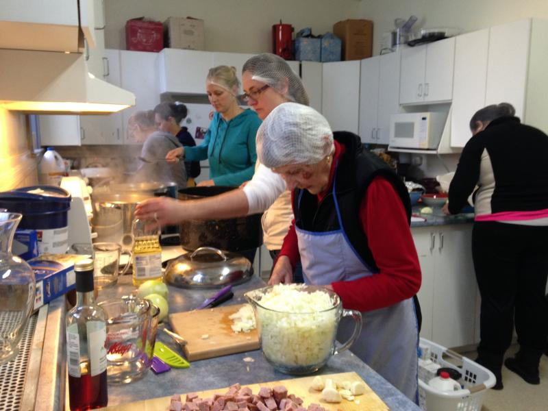 (L-r): Margaret Nussbaumer, Carrie Vroege, and Lydia Mans preparing a meal for the community kitchen with Emily Geertsema and Patricia Van Donkelaar in the background.