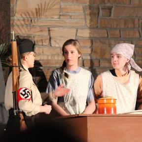 A Nazi soldier takes food from young Ina's family while Ina's brother is disguised as a girl.