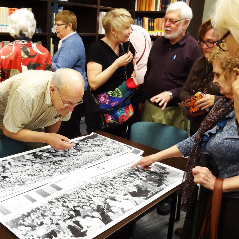 West End CRC seniors gather around a photo at the Gerry Segger Heritage Collection.
