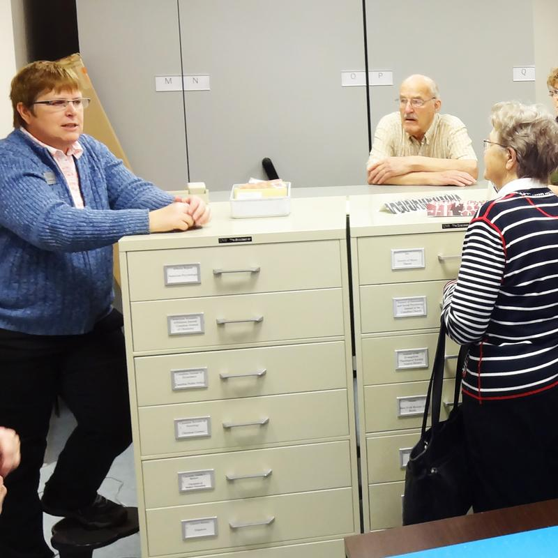 Archivist Bonita Bjornson talks to West End CRC seniors at the Gerry Segger Heritage Collection.
