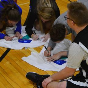 Special Olympic athletes collect autographs from Thomas More College basketball players.