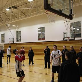 Players from Tufts University cheer on Special Olympic athletes during a shooting drill.
