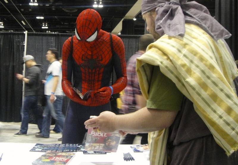 "Spiderman buys a ""Story of Jesus Christ"" comic from Jeremy Williamson, who is dressed as the apostle Paul."