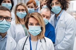 Group of doctors with face masks looking at camera, corona virus concept
