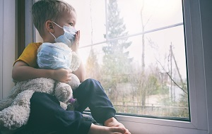 Child in window with mask