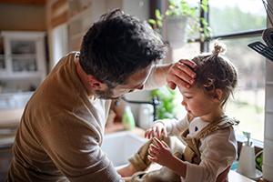 father checking sick daughter's temperature