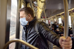 man wearing disposable medical face mask in car of the subway