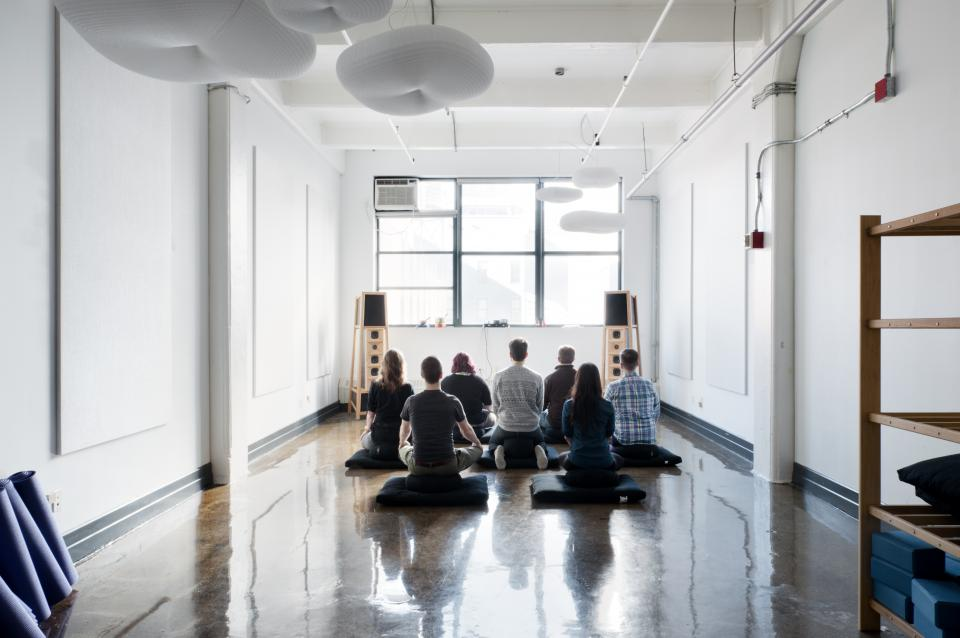 Employees meditating in our Breathing Room, where they can go when they need some quiet. We also host twice-weekly yoga classes here.