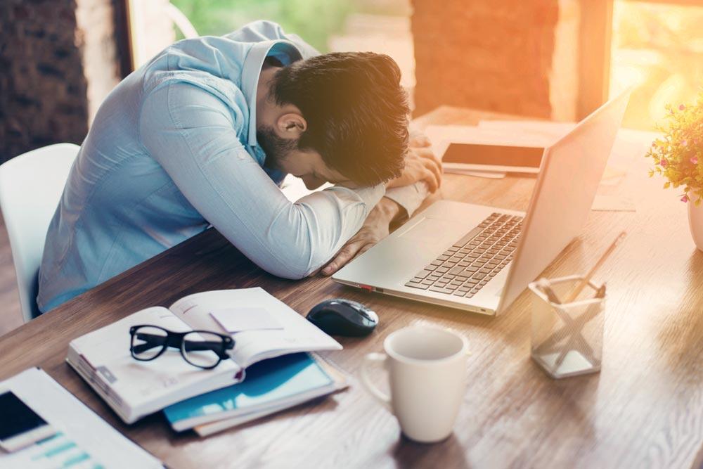 hombre cansado con enfermedad laboral