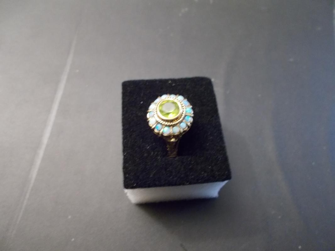 Ladies 14 Karat Yellow Gold Ring Containing One Round Bezel set Peridot and 14 Opals