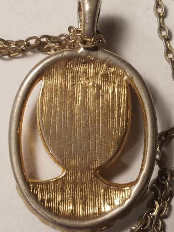 A 1960 to 1970s gold tone and plastic cast cameo pendant necklace on a long chain