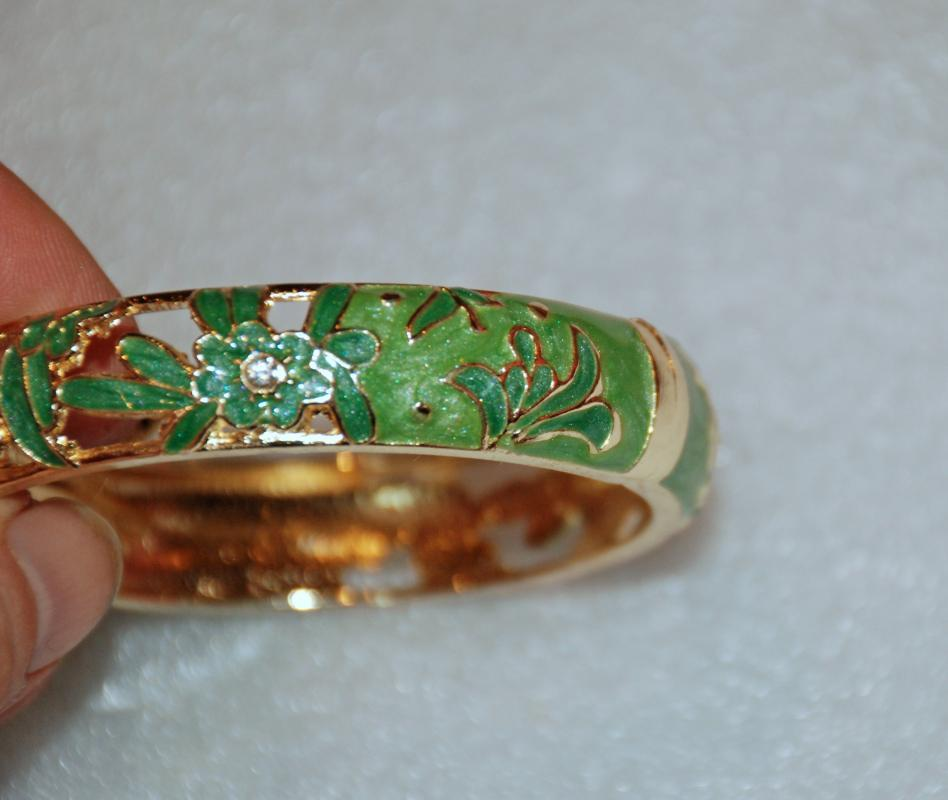 Hinged Bracelet with Green Enamel Floral cut out and rhinestones set in gold tone