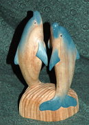 Handcrafted wood carving of two dolphins