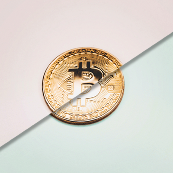 A photo of a physical Bitcoin against a pink and green background.