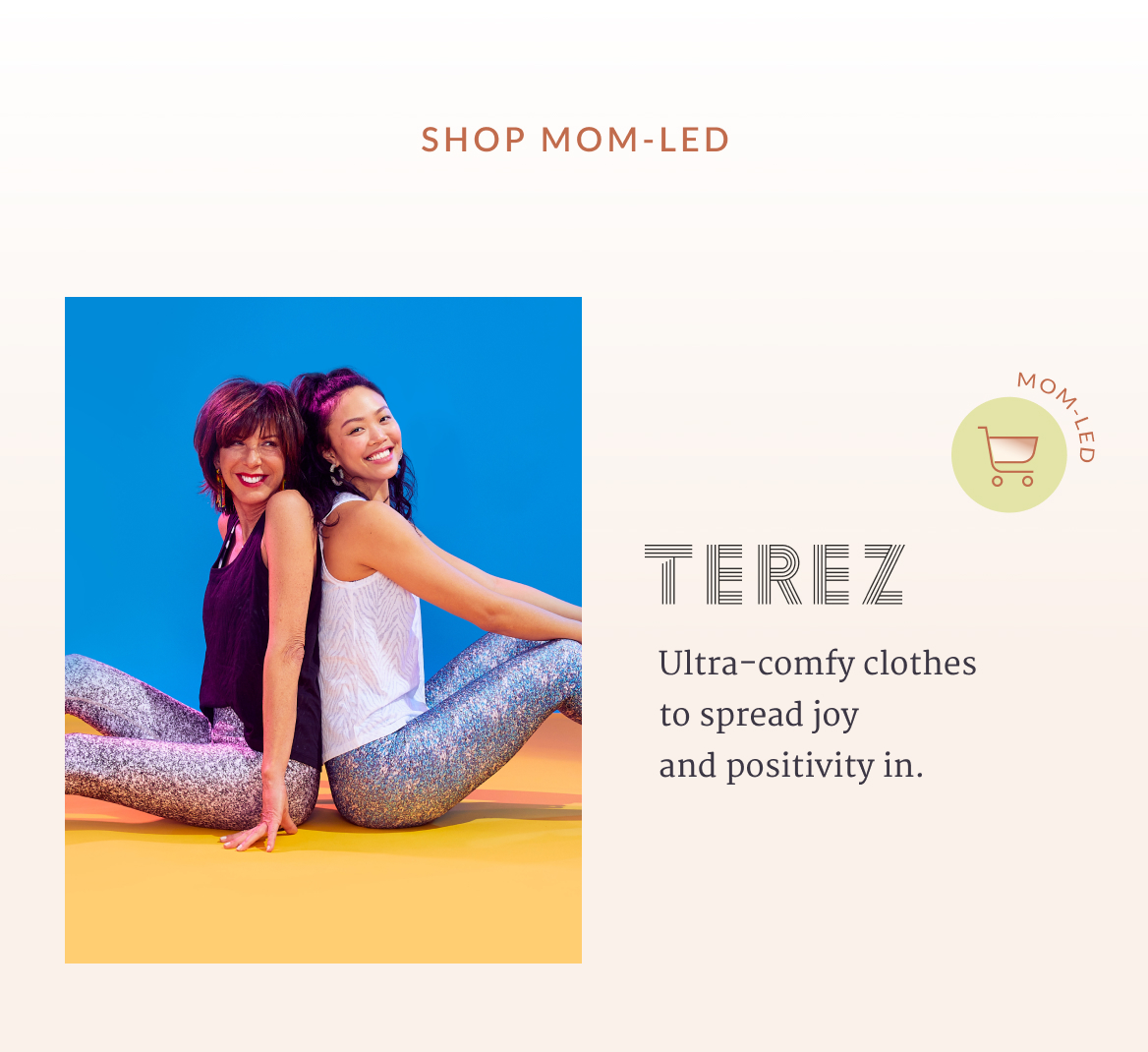 Ultra-comfy clothes to spread joy and positivity in. Two women smiling and sitting back-to-back on the floor.