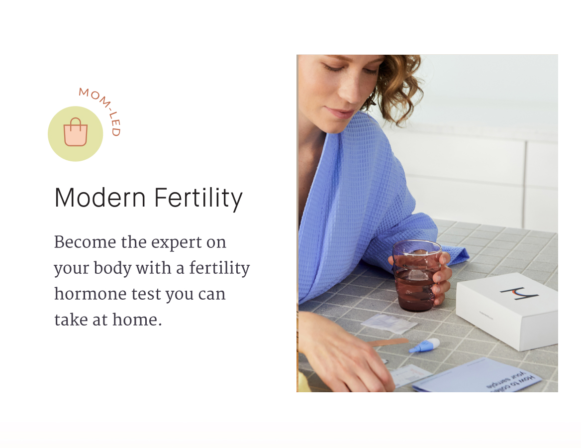 Become the expert on your body with a fertility hormone test you can take at home. A woman holding a glass and looking down at an arrangement of paper on a tabletop.