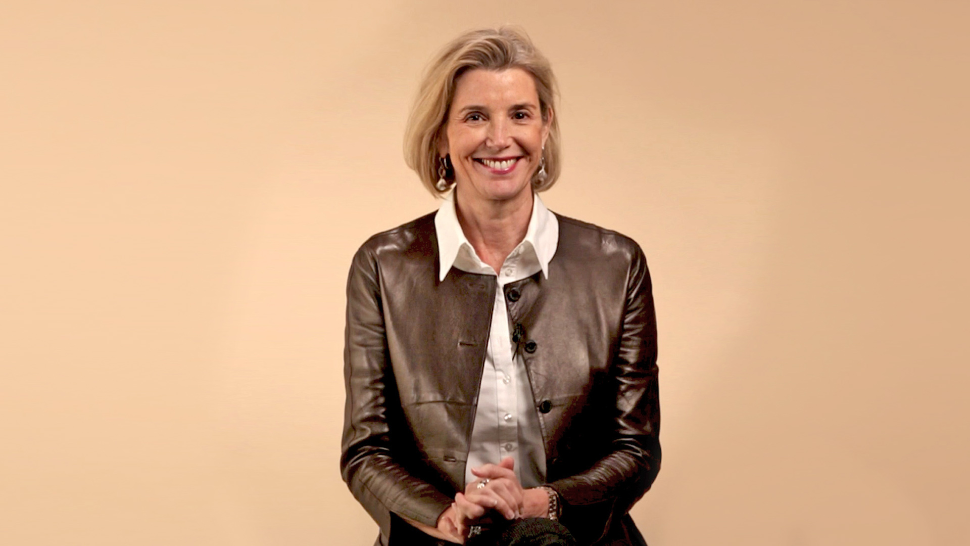 A freeze frame of CEO Sallie Krawcheck, smiling into the camera and wearing a brown leather jacket. Photo.