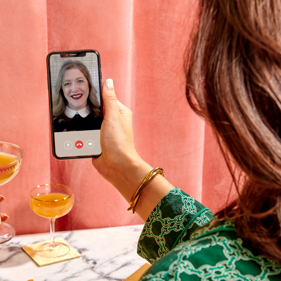 A woman holding a smartphone and video calling with another woman. Evening beverages in the background. Photo.