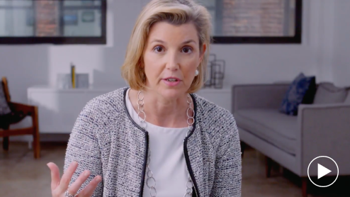 Ellevest CEO Sallie Krawcheck sitting in front of office furniture with a play button arrow overlay. Photo.