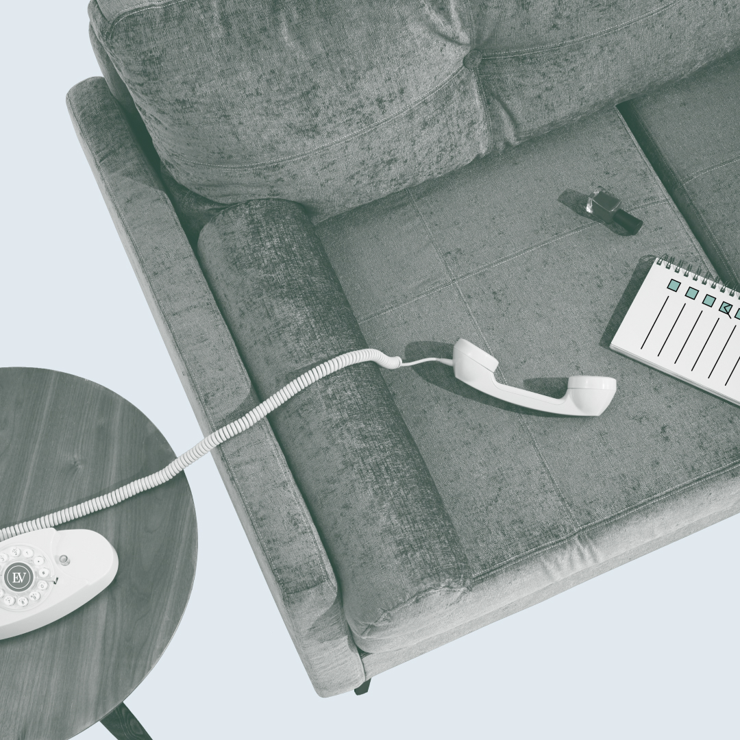 A photo of a spiral-corded phone off the hook and lying on a couch, with a notebook and bottle of nail polish nearby.