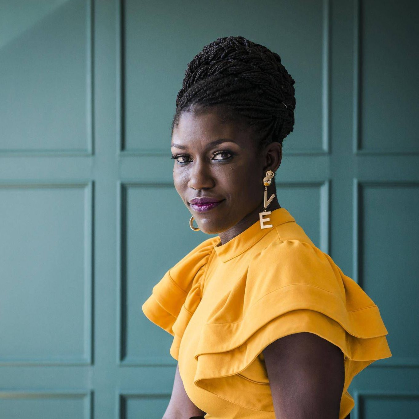 """A photo of Bozoma St. John wearing a yellow shirt and earrings that spell out """"LOVE"""" sitting in front of a teal wall."""