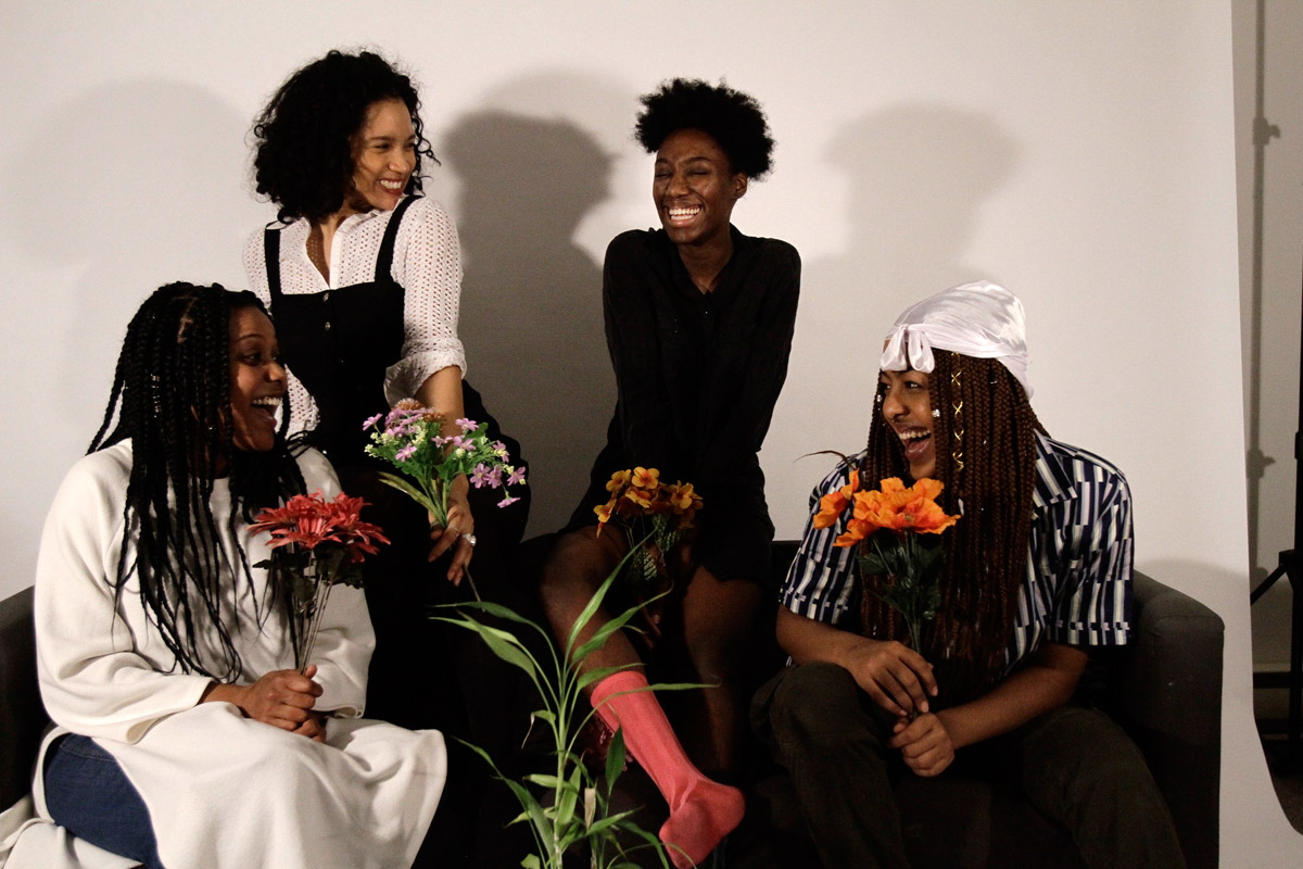 Four women holding flowers laughing on the couch