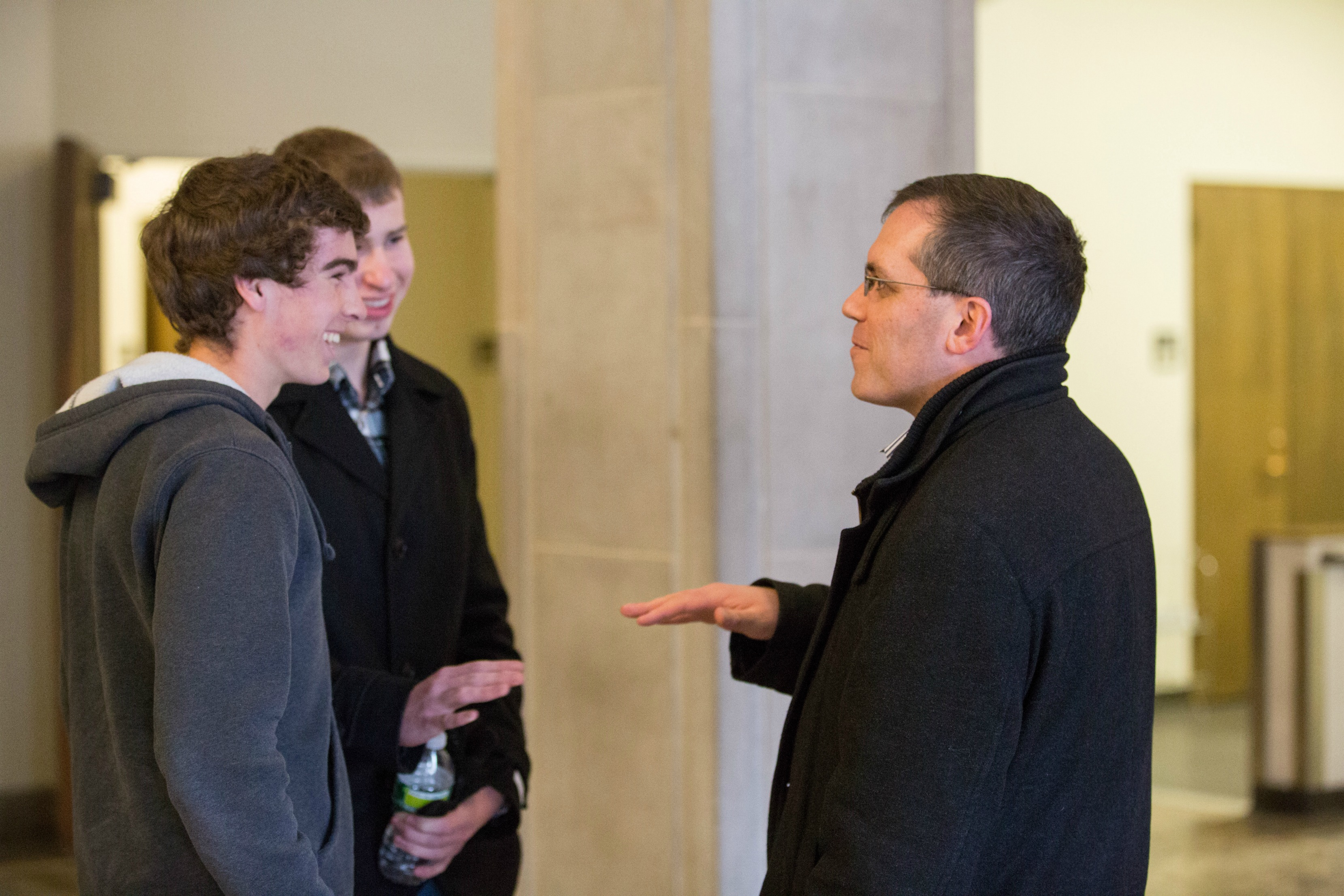 picture for Economics Leadership Member, Dan Braga discusses his Economics 108 lecture with two students