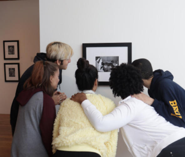 Five students huddling around a picture in a gallery