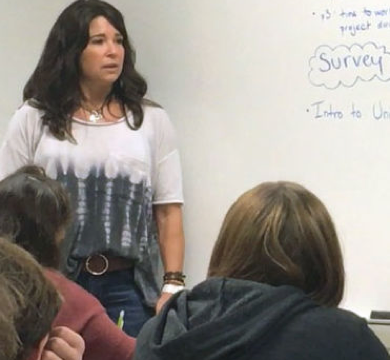 Photo of Ali O'Brien speaking to students in front of a whiteboard.
