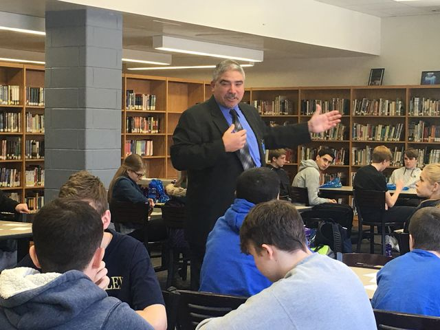 Photo of Nick Nicolaides speaking to a group of students inside a school library.
