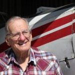 Caption: Harold Blackledge, a 79-year-old agricultural pilot, stands in front of his 1975 Piper Pawnee Brave in one of his hangars at the Watonga Regional Airport. The drought — the worst he's seen — has dried up aerial spraying work in Oklahoma, he says., Credit: Joe Wertz